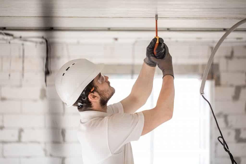 חשמלאי עם קסדה לבנה עובד על חשמל בתקרה