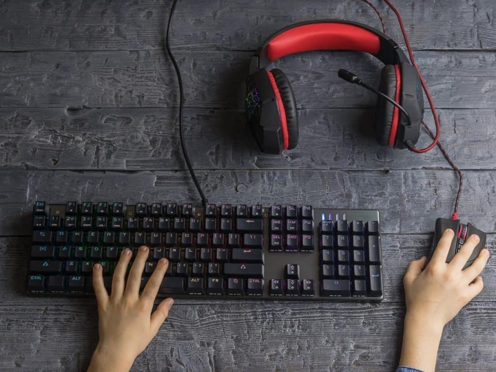 ידיים של ילדה משחקות במחשב ואוזניות מונחות על השולחן