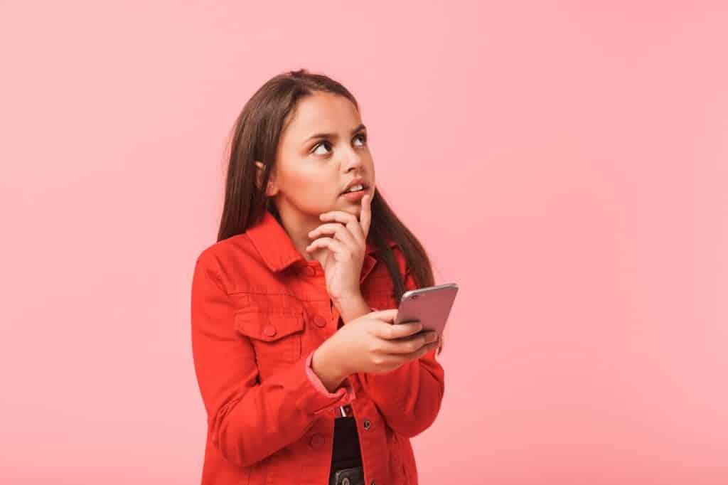 ילדה עם ג'קט אדום מחזיקה את הסנטר בהבעת שאלה