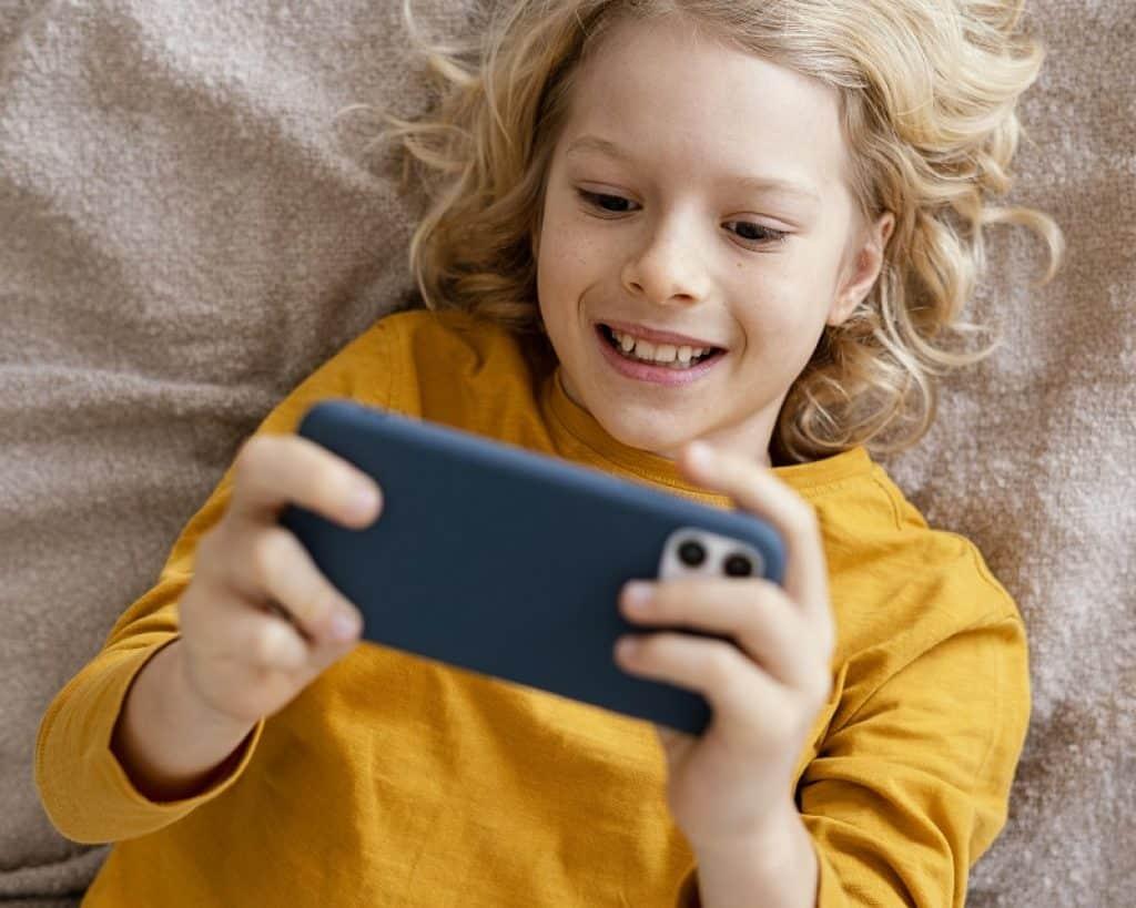 ילד בלונדיני עם חולצה צהובה משחק בטלפון