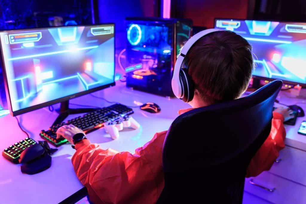 ילד גיימר עם שני מסכים ותאורה צבעונית תוך כדי משחק