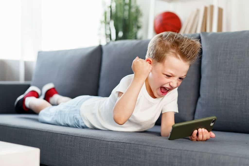 ילד עם בגדים לבנים ונעליים אדומות שמח שניצח במשחק
