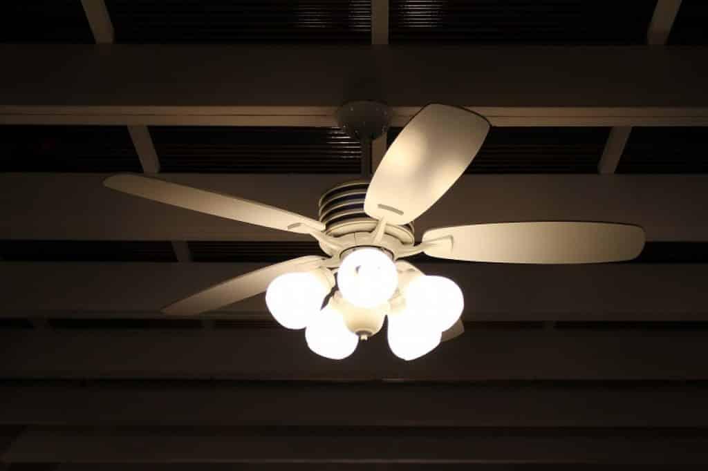 מאוורר תקרה עם מנורות דולקות תלויות על פרגולה לבנה
