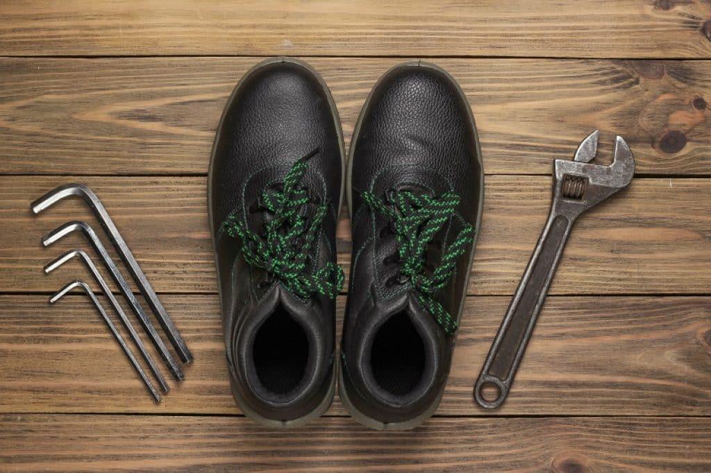 נעלי הליכה ועבודה מעור מונחות על פרקט וכלים ליד
