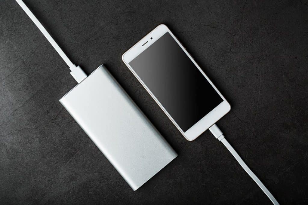 סוללה וטלפון מונחים על שולחן ומחוברים לחשמל