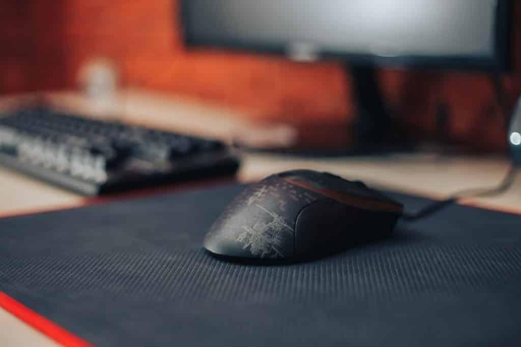 עכבר גיימינג על פד ומקלדת מונחים על שולחן מחשב