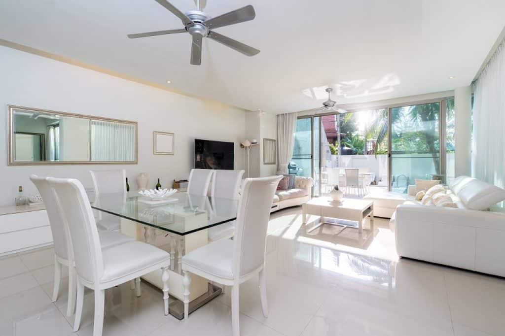 צילום של פינת אוכל וסלון בבית עם עיצוב לבן