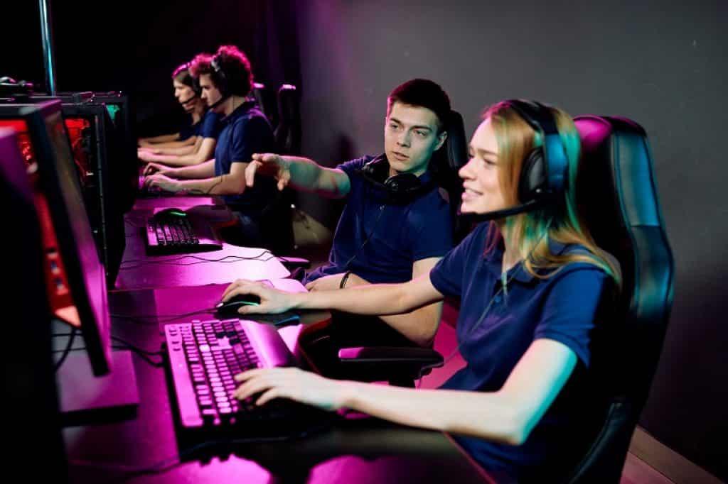 צעיר וצעירה תוך כדי משחק מחשב עם תאורה צבעונית ואוזניות
