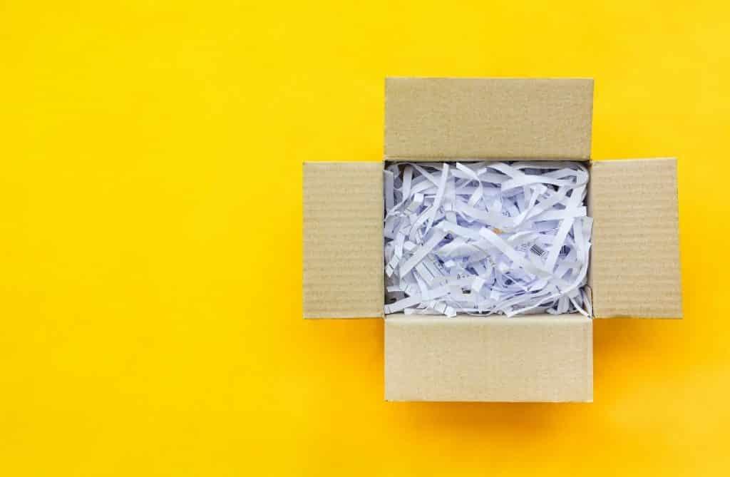 קופסא עם דפים חתוכים על רקע צהוב