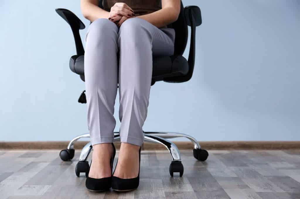 רגליים של אישה יושבת על כיסא משרדי