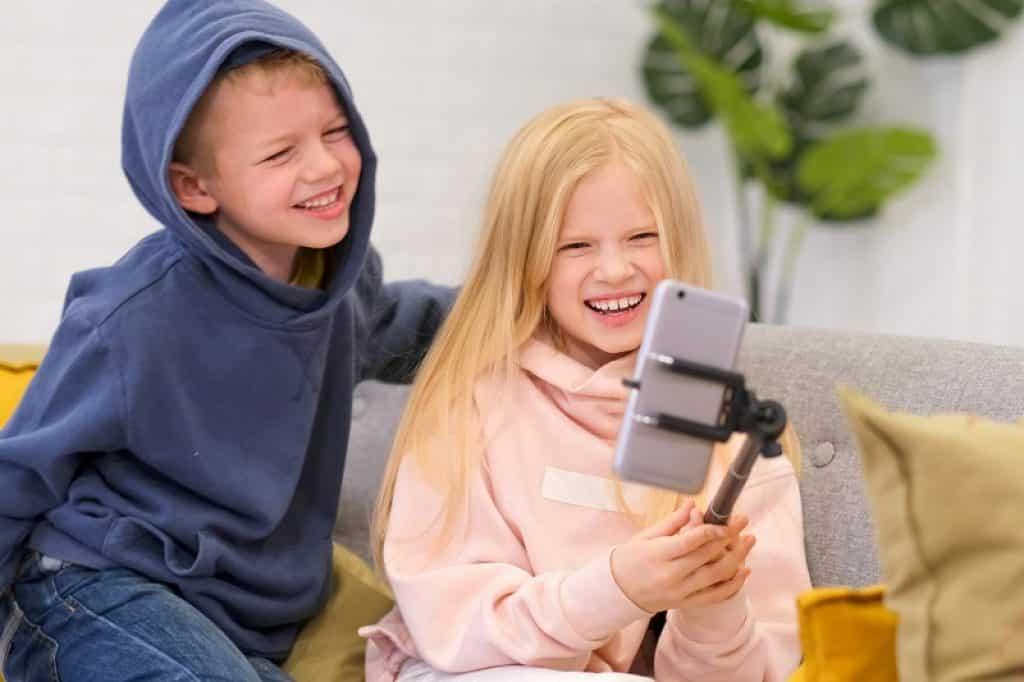 שני ילדים עושים שיחת וידאו עם מוט סלפי