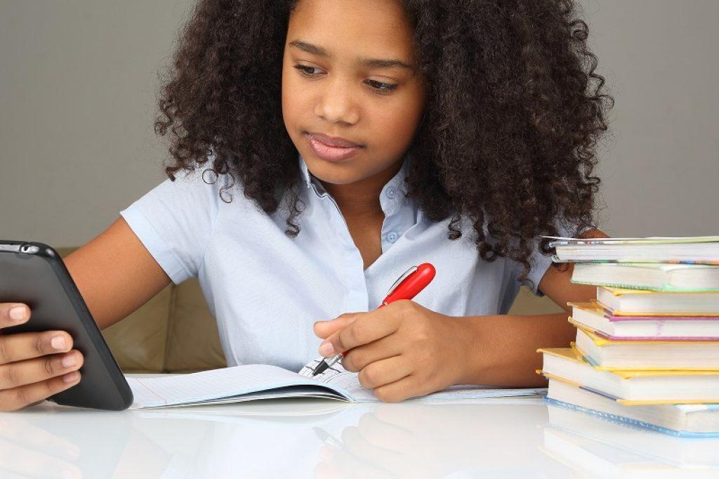 תלמידה מחזיקה עיפרון אדום ומכינה שיעורי בית