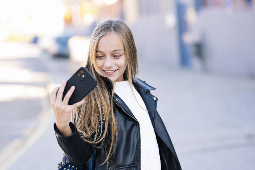 תלמידה עם מעיל שחור בשיחת וידאו בדרך לבית הספר