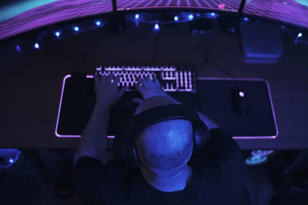 תמונה של גבר מקליד ממבט על בחדר חשוך ותאורת לד צבעונית