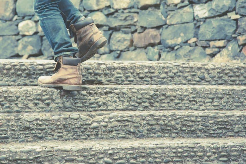 תקריב של רגליים עולות במדרגות אבן