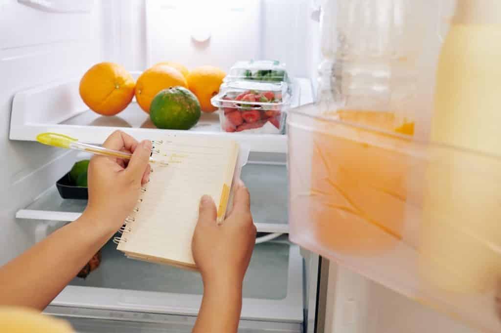 אישה בודקת איזה מוצרים חסרים בבית ועושה רשימת קניות