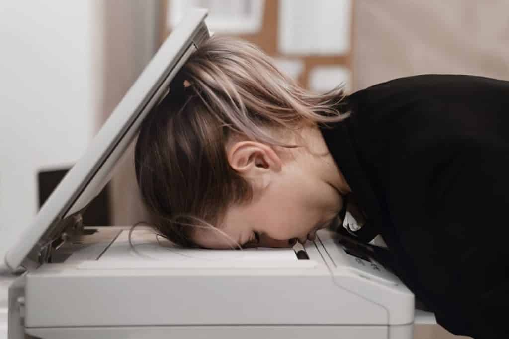 אישה בלונדינית שהכניסה את הראש לתוך מכונת צילום מרוב ייאוש