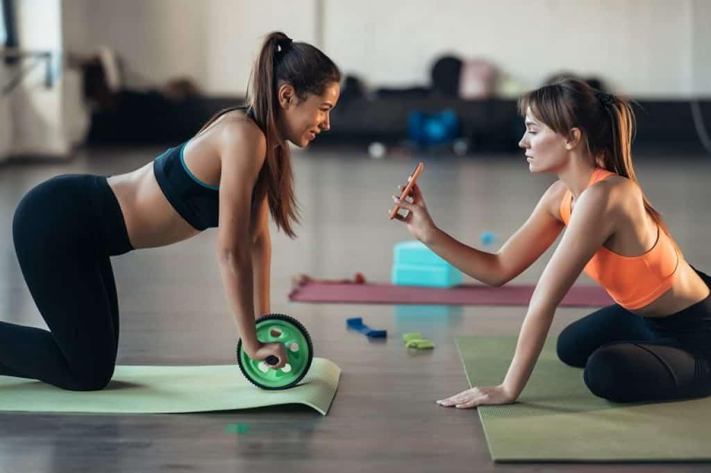 אישה לובשת בגדי יוגה ונשענת על גלגל אימון לבטן
