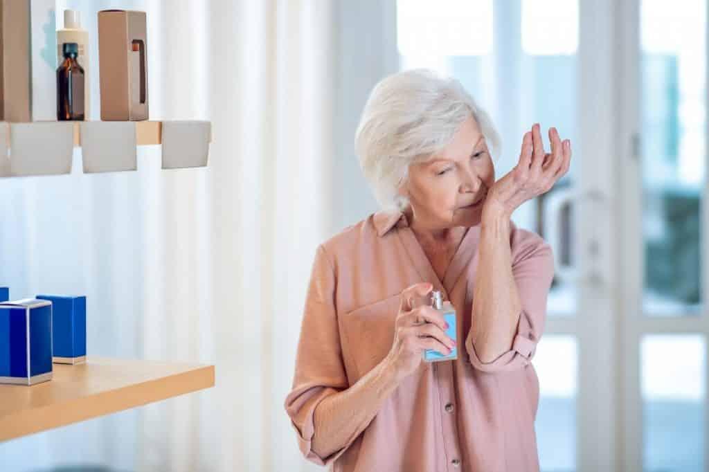 אישה מבוגרת מריחה טסטרים בחנות יופי ומתלבטת במה לבחור