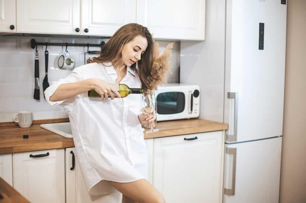 אישה מוזגת יין שהוציאה מתוך מקרר יין