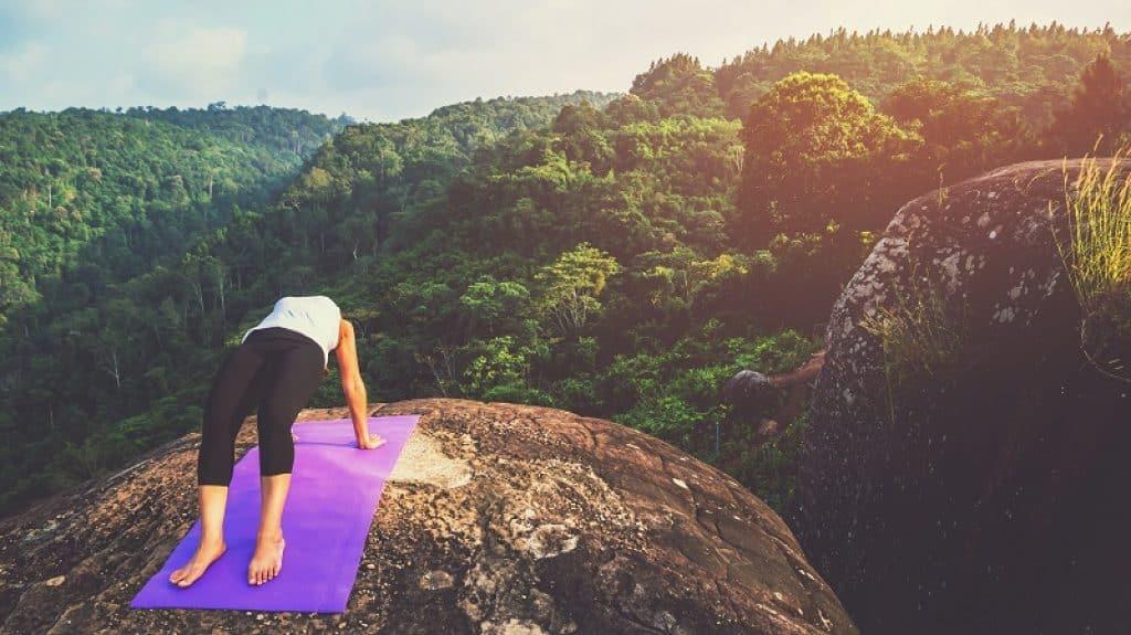 אישה מתאמת על צוק בחיק הטבע על מזרון בצבע סגול