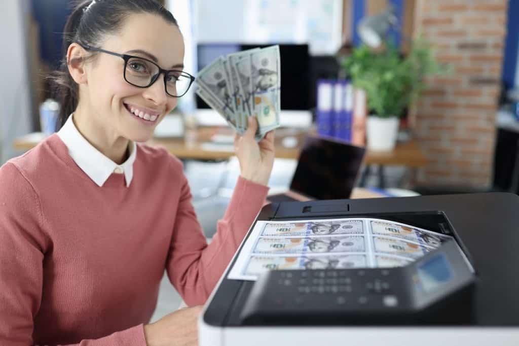אישה עם סוודר ורוד ומשקפיים מחזיקה כסף מודפס ומחייכת