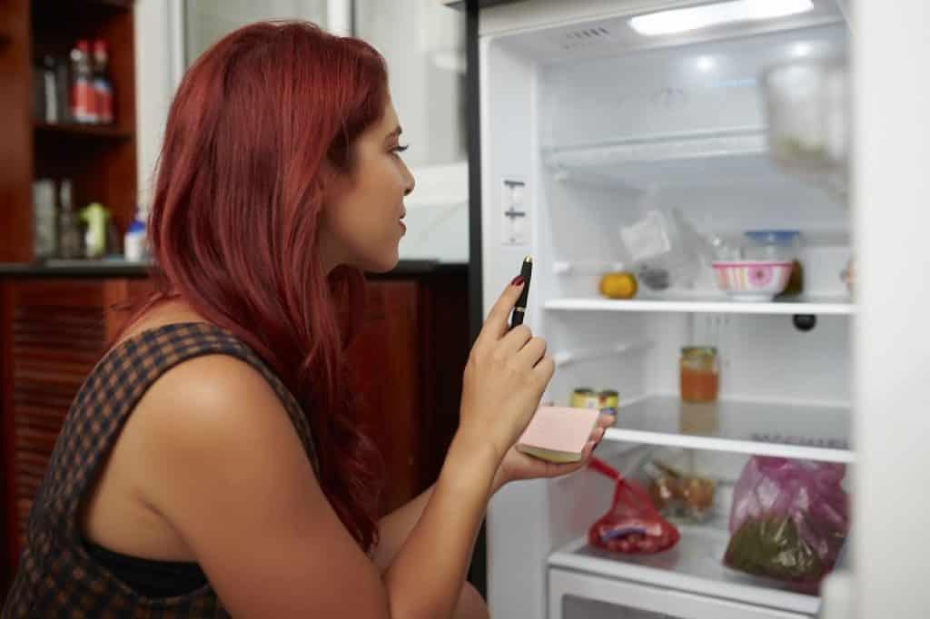 אישה עם שיער אדום מחזיקה עט ופנקס ועושה רשימת קניות