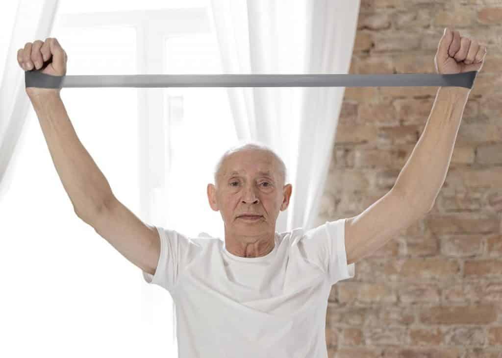 איש מבוגר מתאמן על הידיים עם גומיית התנגדות אפורה