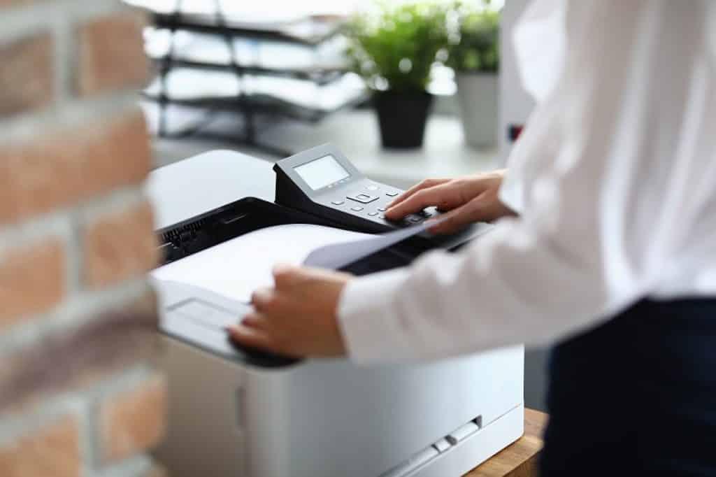 איש עסקים עם חולצה לבנה מוציא דפים מתוך מדפסת HP