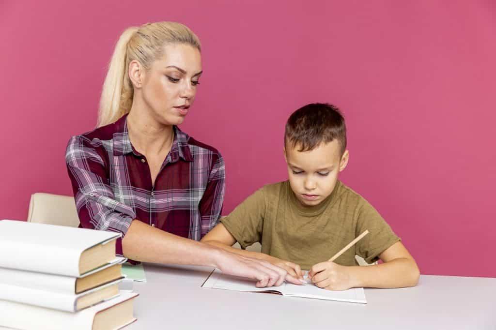 אמא שלובשת חולצה משובצת עוזרת לילד להכין שיעורי בית