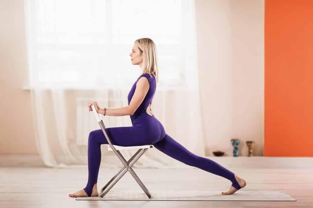 בחורה לובשת אוברול בצבע סגול ומתאמנת עם כיסא