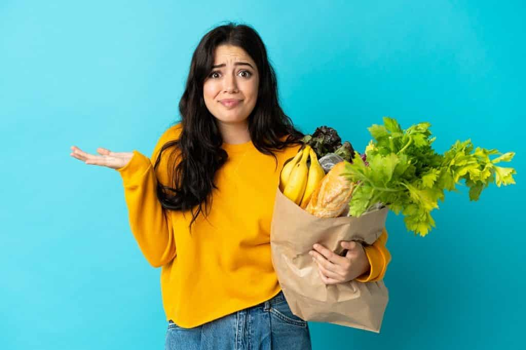 בחורה מחזיקה שקית עם מצרכים ועושה תנועה של שאלה