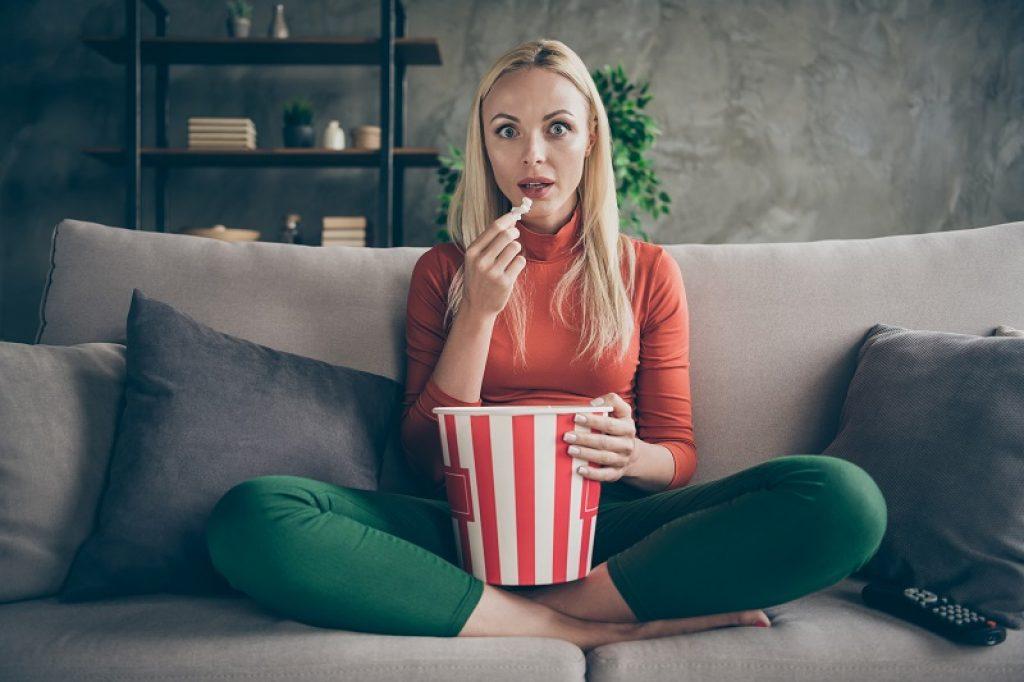 בחורה עם חולצה אדומה יושבת על ספה ואוכלת פופקורן
