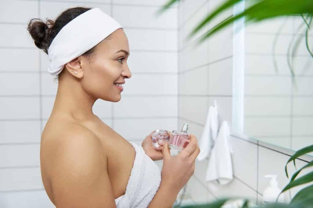 בחורה עם חלוק מסתכלת במראה במקלחת