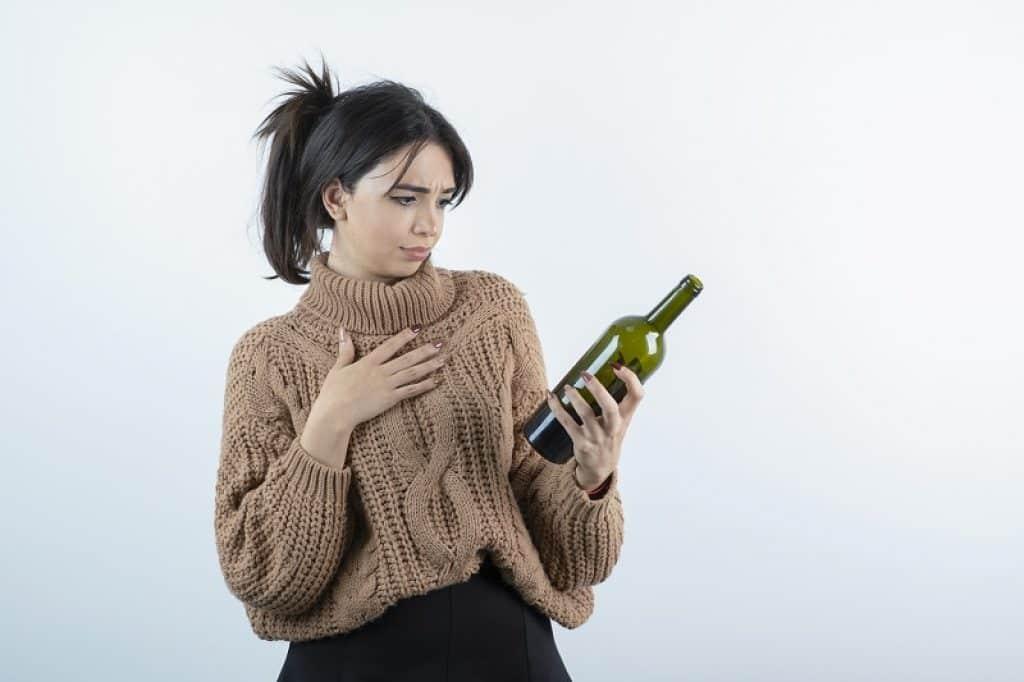 בחורה עם שיער אסוף מסתכלת על בקבוק במבט של שאלה