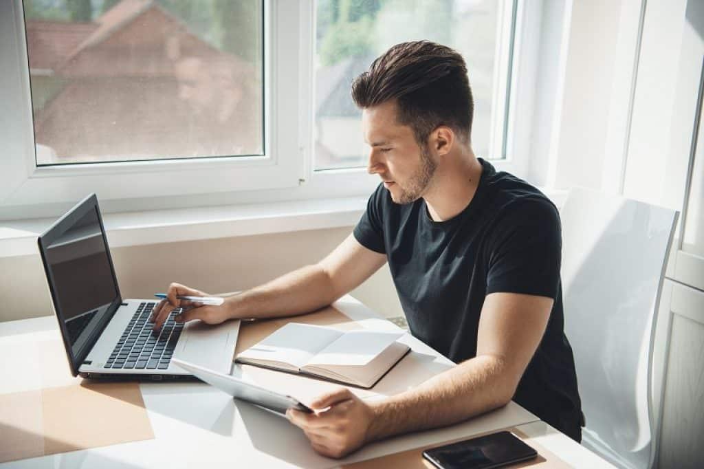 בחור עם חולצה שחורה מכין שיעורי בית על שולחן כתיבה