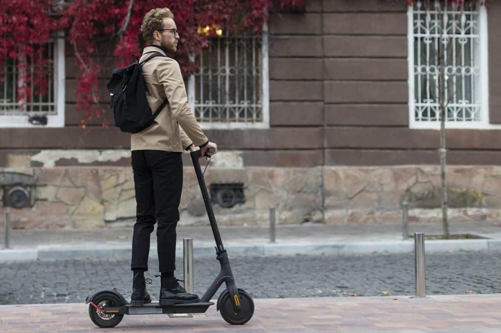 בחור צעיר עם תיק גב ומשקפי שמש בדרך לעבודה