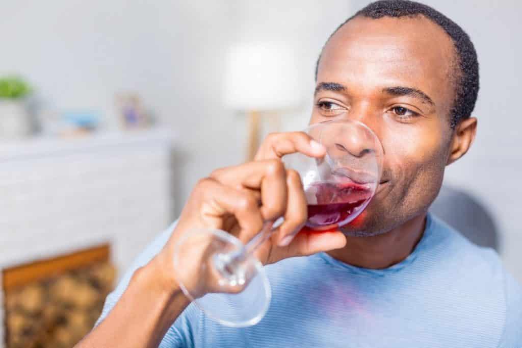 בחור שחום שותה מכוס עם רגל גבוהה