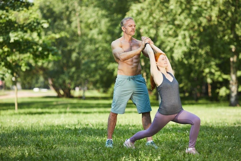 בעל ואישה מתאמנים בחוץ באור יום ולובשים בגדי יוגה