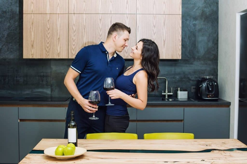 בעל ואישה עם חולצות כחולות מתחבקים במטבח