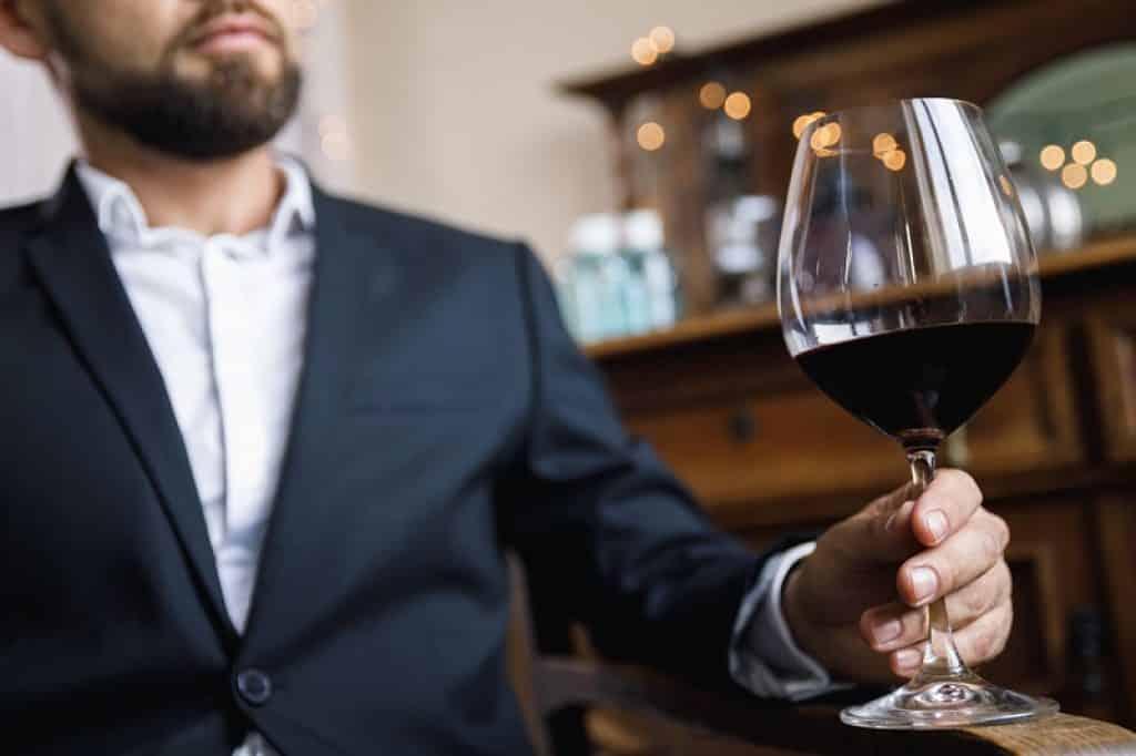 גבר בחליפה יושב בפאב ומחזיק כוס ביד