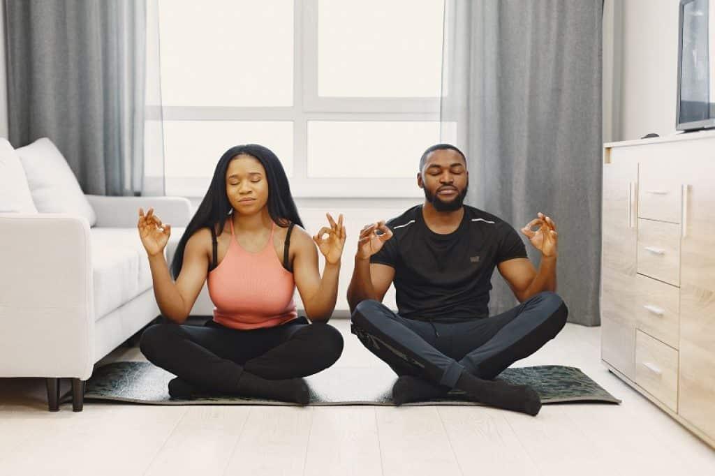 גבר ואישה יושבים על מזרון שחור ולובשים בגדי יוגה