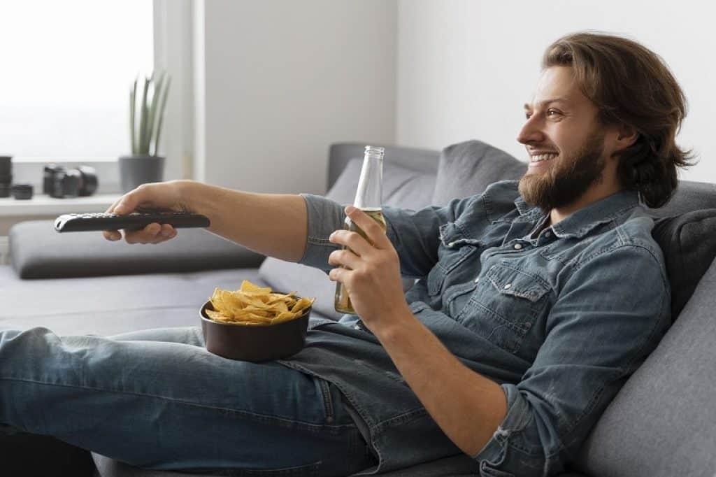 גבר יושב על ספה מנשנש ומעביר ערוצים בשלט