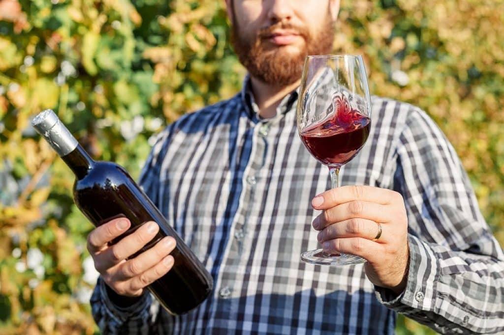 גבר מחזיק בקבוק ביד אחד וכוס ביד השנייה