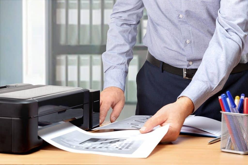 גבר עם חולצה מכופתרת בצבע תכלת מוציא תדפיסים ממגש של מדפסת HP
