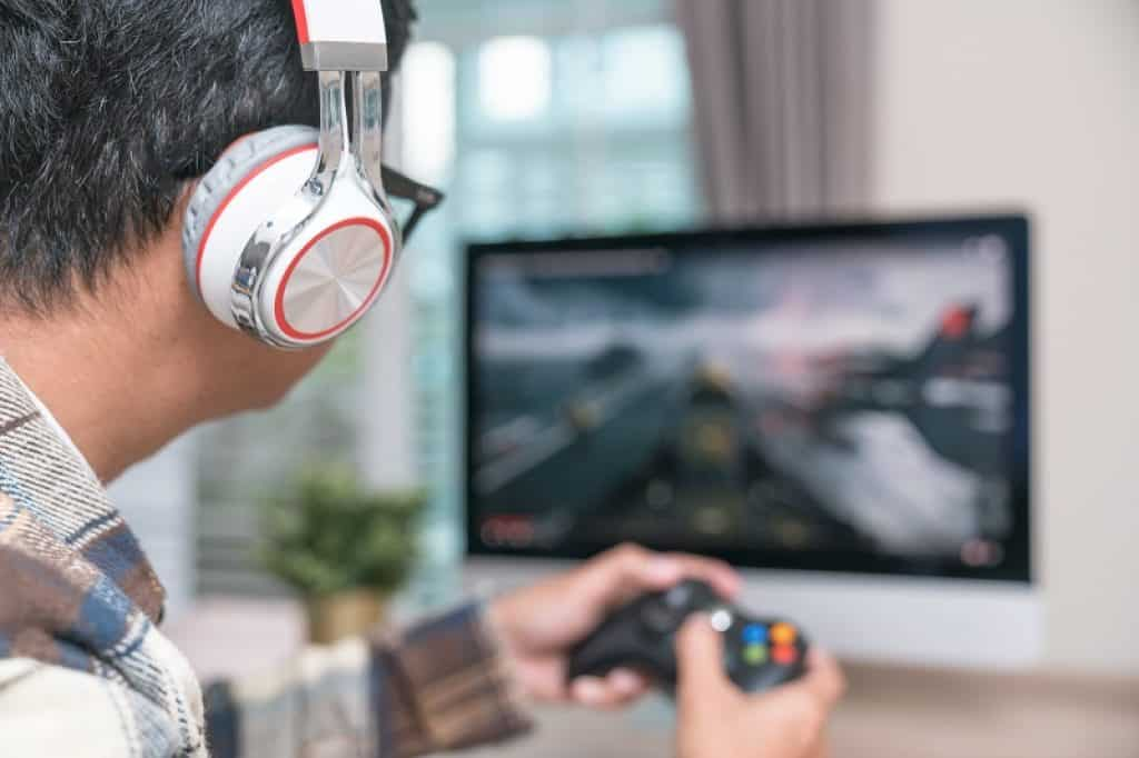 גבר עם חולצה משובצת ואוזניות משתמש במסך מחשב לגיימרים