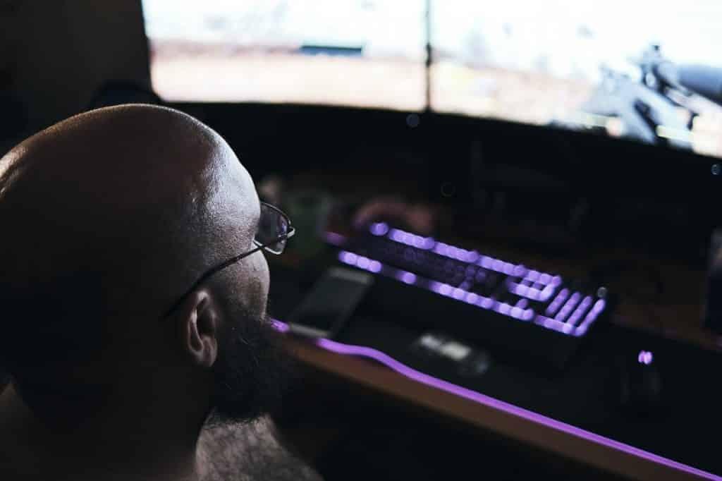 גבר עם קרחת ומשקפיים יושב ליד מקלדת מוארת