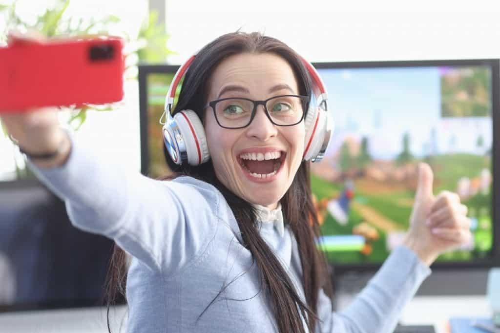 גיימרית עם משקפיים ואוזניות מצלמת סלפי