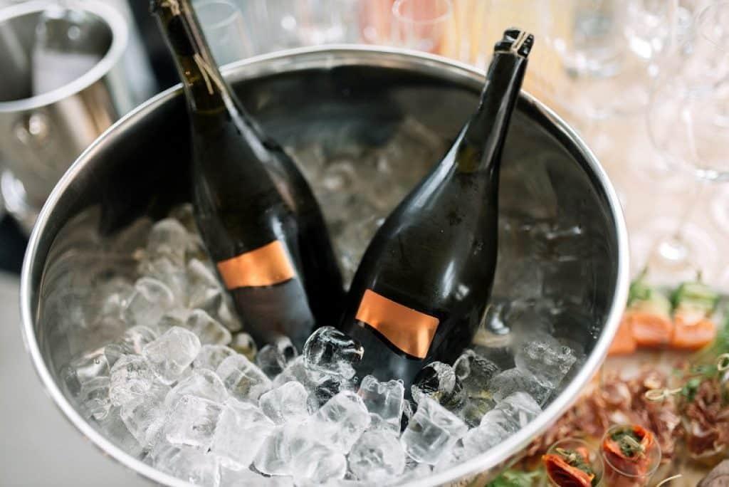 דלי מלא בקרח מקרר יין מונח על שולחן