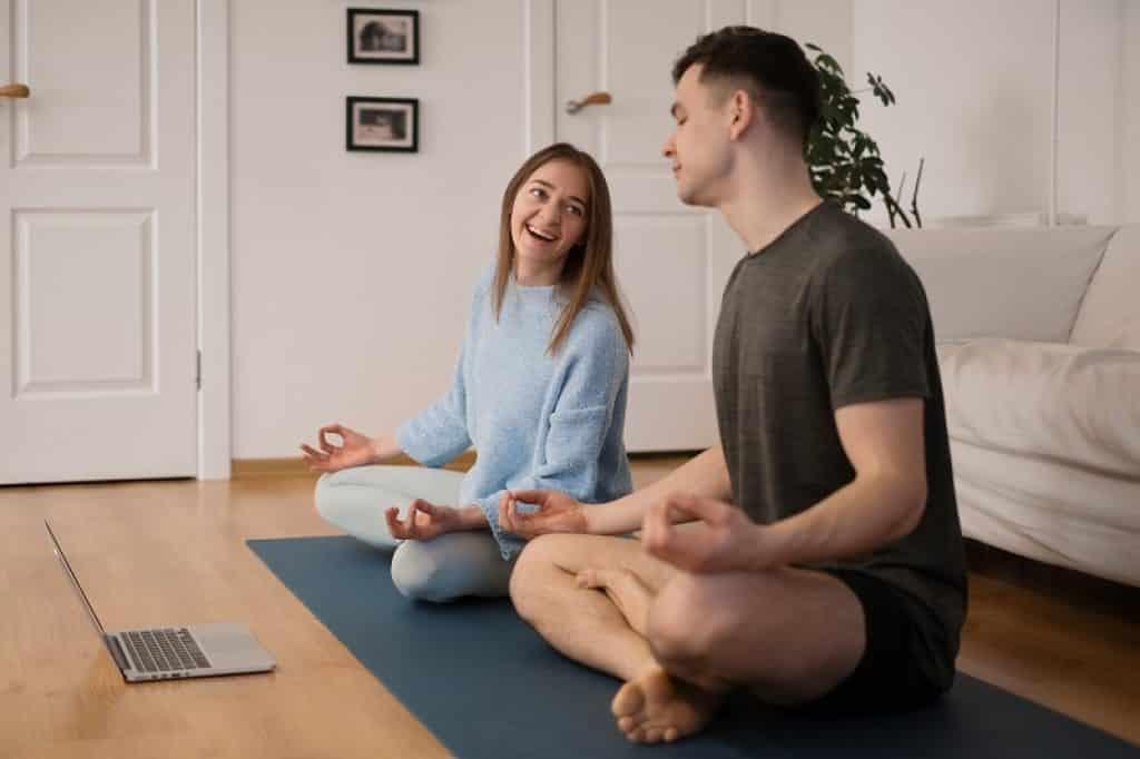 זוג יושבים בסלון עם ספה לבנה וצופים בסרטון הדרכה במחשב
